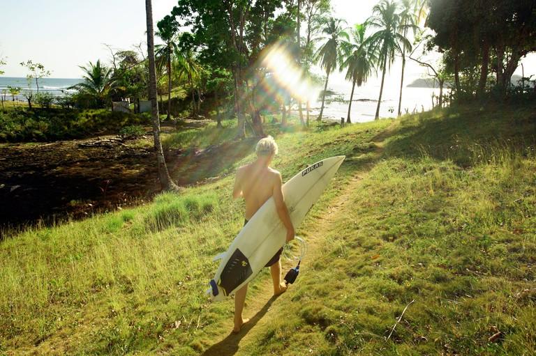 Surfer walks to La Punta in Santa Catalina, Panama