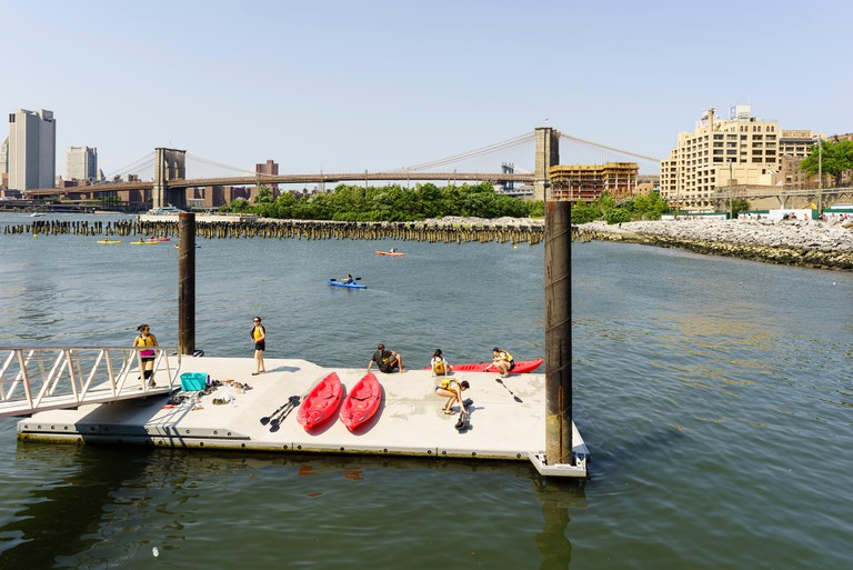 young people setting up their kayaks for a glide Brooklyn Bridge Park Boathouse at the Pier 2 floating dock