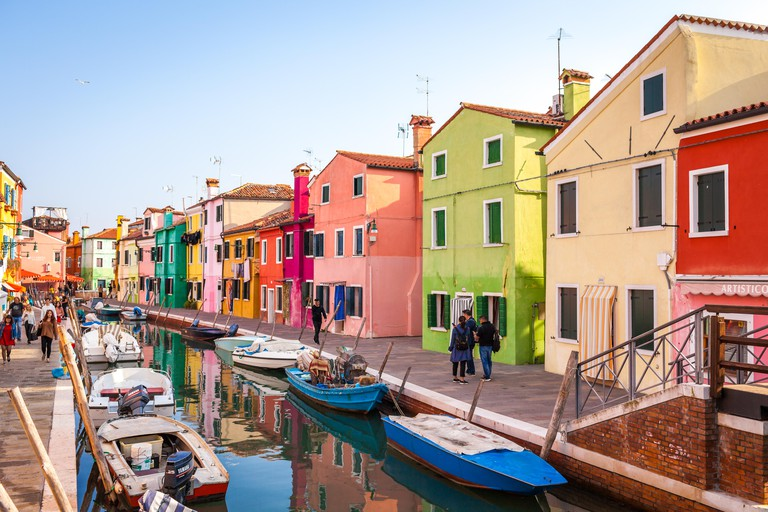 Burano, Italy - October 2018: Tourists walking around the colorful fishermen's houses in Burano - PYD8AD