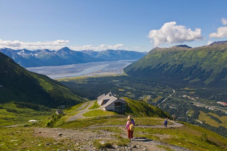 People hiking at the Alyeska Ski Resort in the Chugach Mountains in Girdwood Alaskawith Turnagin Arm in the distance