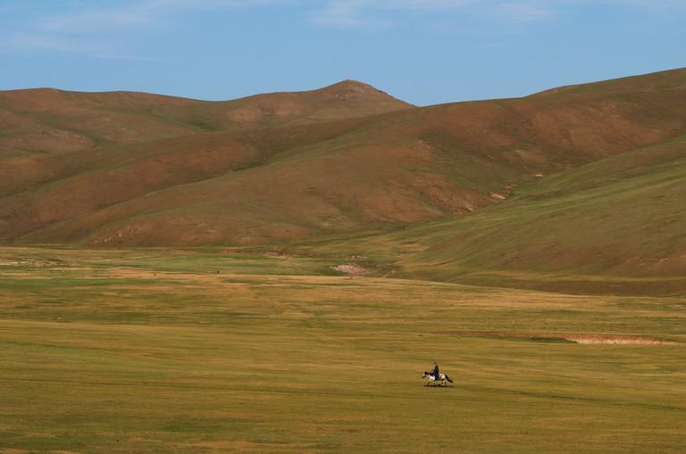 Lone Mongolian horseback rider travels through grasslands, Bogd Khan Mountain Protected Area, Mongolia. Credit Line: © Kraig Lieb