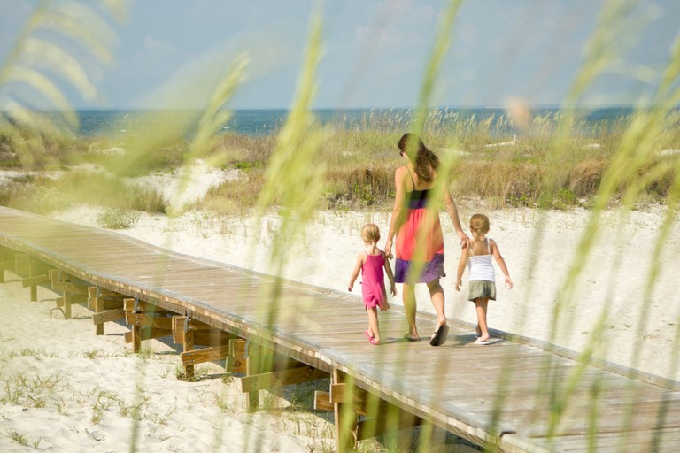 Mother (age 29) and daughters (ages 4 and 5) strolling the boardwalk to the beach. Hilton Head Island, South Carolina (MR)