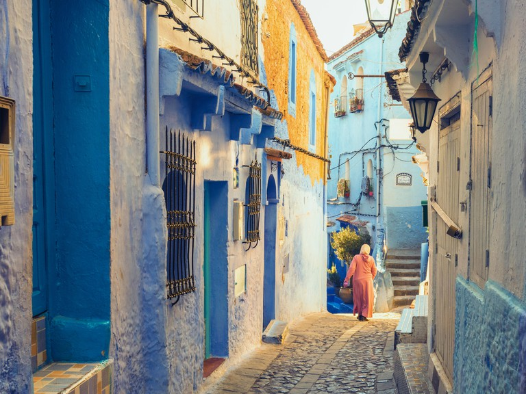 Woman walking in the old city of Chefchaouen with the famous blue buildings, Chefchaouen, Morocco 2A1619F