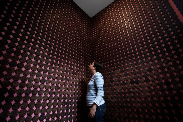 """2D0GDDY A woman stands next to more than 2,000 chocolate samples adhered to the walls inside """"Mucho"""", a chocolate museum, in Mexico City October 29, 2013."""