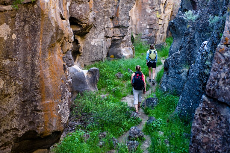 Two women hike through Crack In the Ground, a volcanic fissure near Christmas Valley, Oregon.