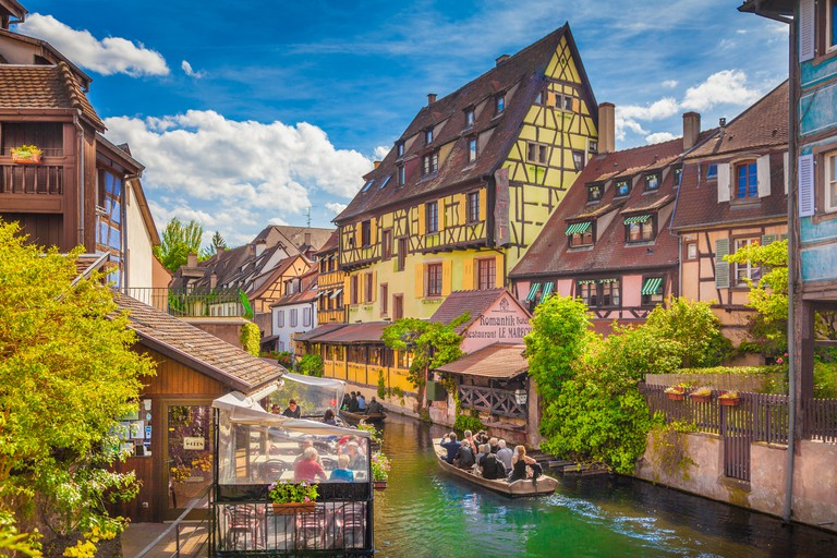 Beautiful view of the historic town of Colmar, also known as Little Venice, with tourists taking a boat ride on river Lauch, Alsace region, France - HNPX94