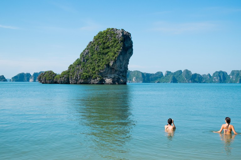young couple swim in the waters around Cong Do island in Halong bay, a world heritage site,Vietnam,Asia.