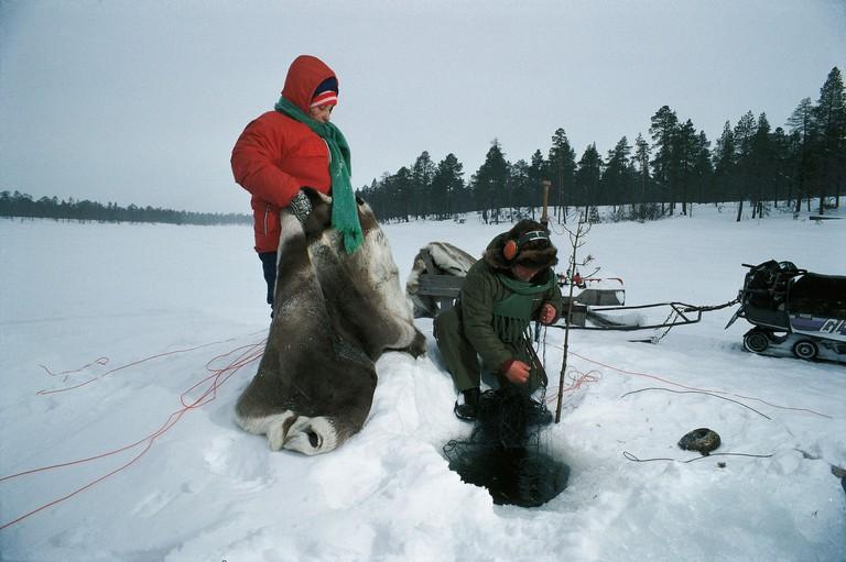 FINLAND, INARI: Fisherman on a frozen lake