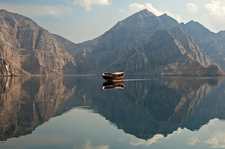 Traditional dhow sailboat moored in a bay during a cruise in the Khor Ash Sham Fjord, Musandam, Sultanate of Oman