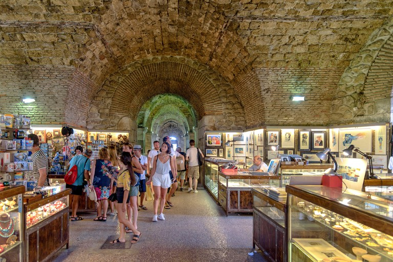Tourists shopping in the market that exists in the cellar of Diocletian's Palace in Split, Croatia