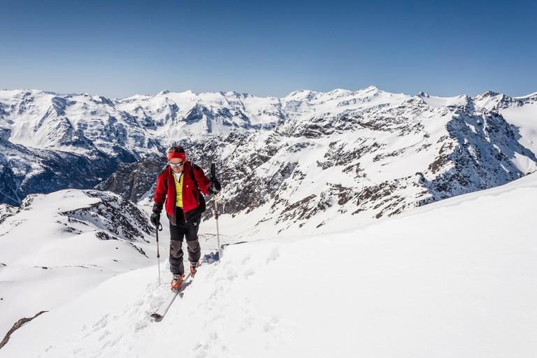 Ski tourer standing on the summit ridge of Laaser Spitze mountain, Stelvio National Park, Veneziaspitze mountain, Zufallspitze