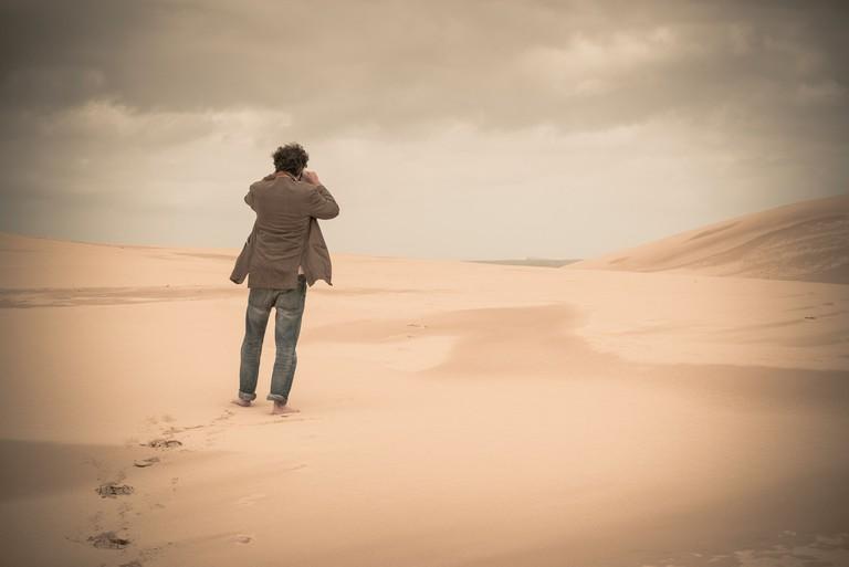 Australia, New South Wales, Woromi Conservation Lands, barefoot man taking photo in desert