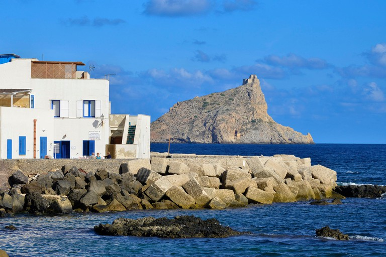 Italy, Sicily, Egadi islands, island of Marettimo, breakwater on sea front with Pointe Troia and its castle in background