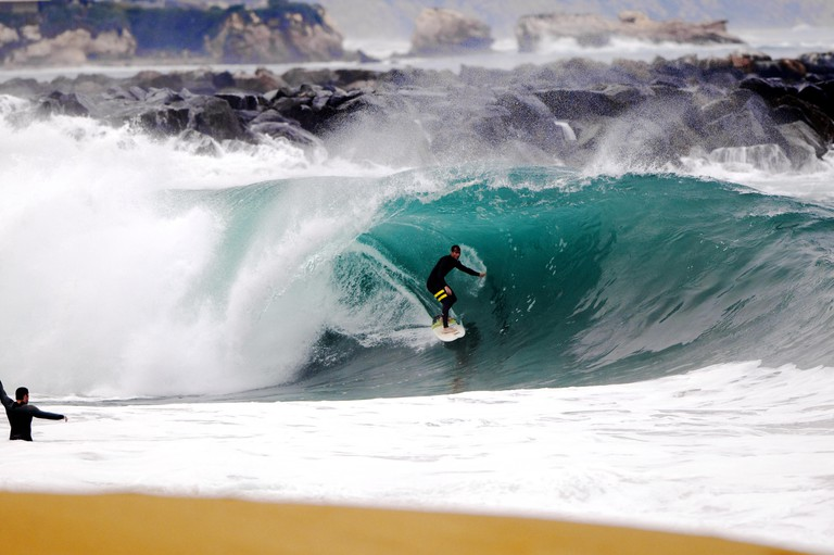 A local surfer pulls into a heavy, shore breaking barrel in shallow water at the surf break The Wedge, in Newport Beach, CA