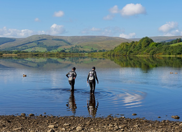 Two women in wetsuits wading into Semerwater, England UK