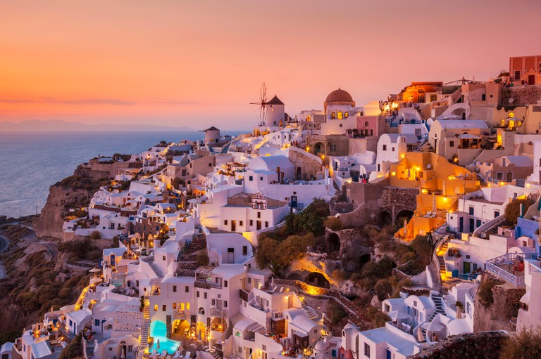 Windmill & white houses at sunset  in the village of Oia, Santorini, Thira, Cyclades Islands, Greek Islands, Greece, EU, Europe
