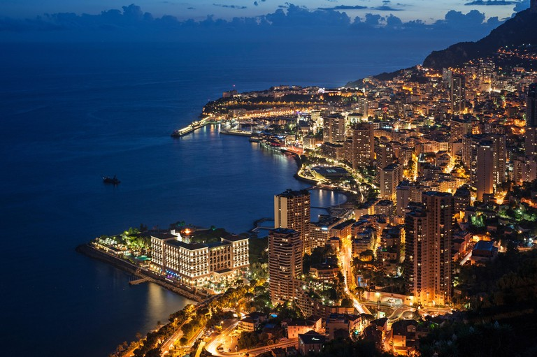 Aerial view over the city and port of Monte Carlo, Monaco along the French Riviera at night, Cote d'Azur
