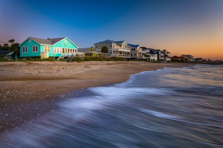 Waves in the Atlantic Ocean and beachfront homes at sunrise, Edisto Beach, South Carolina.