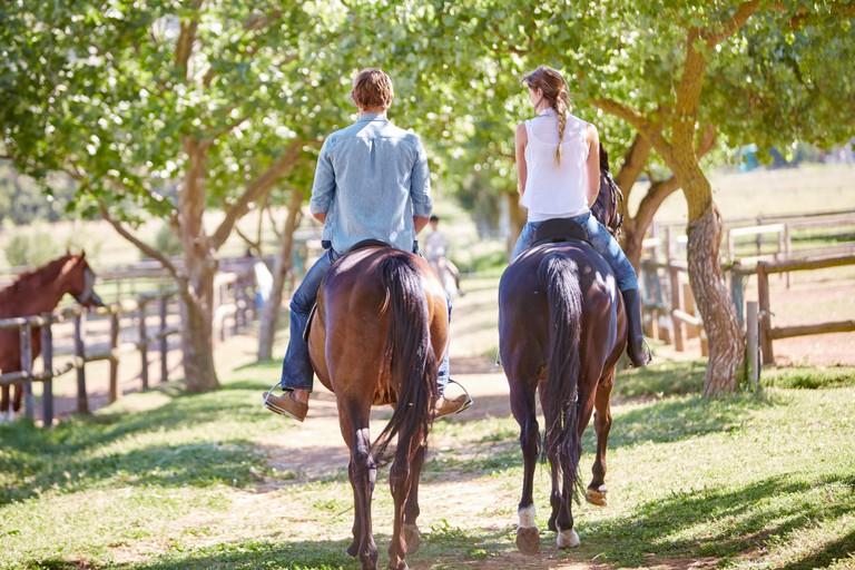 Young couple riding at paddock