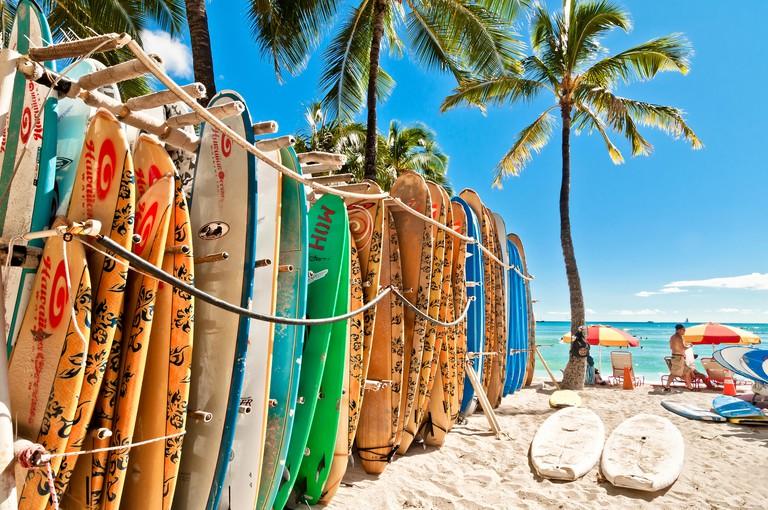 Honolulu, HI, USA - September 7, 2013: Surfboards lined up in the rack at famous Waikiki Beach in Honolulu. Oahu, Hawaii.