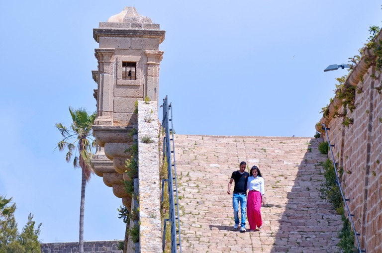 ACRE, ISR - APR 21 2015: Arab couple visit at the walls of Akko.Old Acre is one of the few cities in the world whose walls have remained standing despite attacks by large powerful armies several times