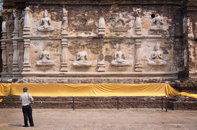 Tourist standing in front of the main chedi at Wat Jet Yod, Chiang Mai, Thailand