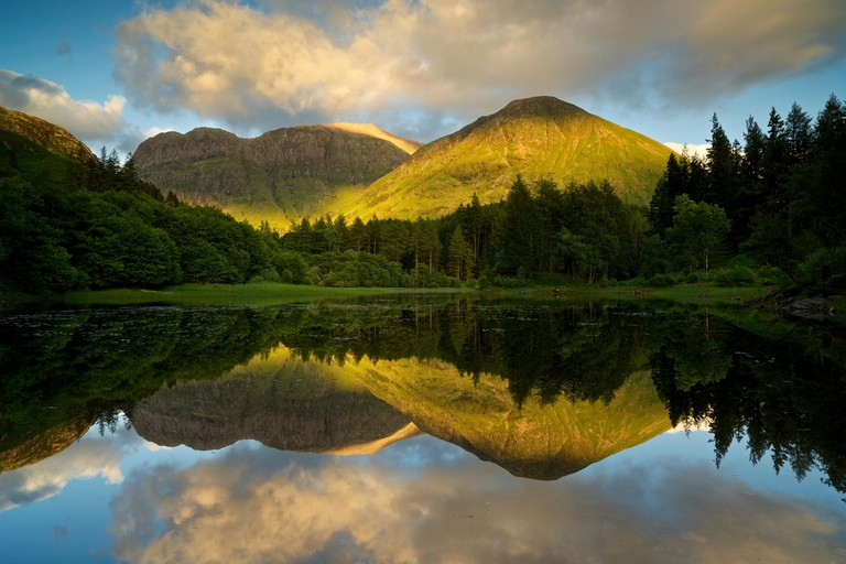 The low dipping sun casts a golden glow on the mountains of Glencoe whilst being reflected in the still Torren Loch
