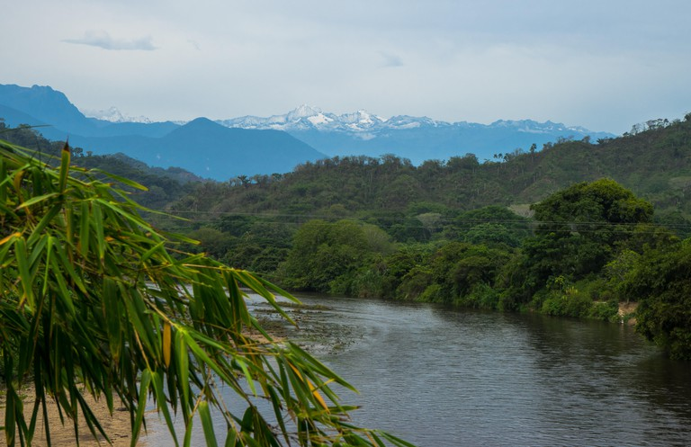 View of the snow-capped Sierra Nevada de Santa Marta Caribbean mountains on Palomino River in Colombia, South America.