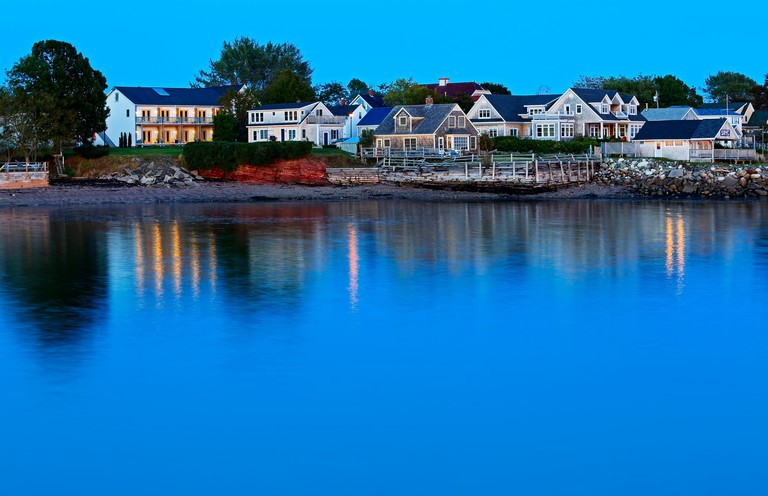Twilight reflections of buildings and lights on waterfront at Saint Andrews, New Brunswick, Canada.
