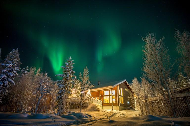 Finland, Lapland, Kittila, Levi, Aurora borealis over cottage