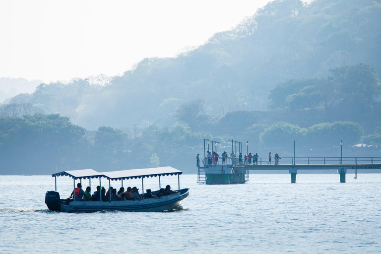 A boat of tourists nears the dock on Lake Catemaco, Veracruz, Mexico.