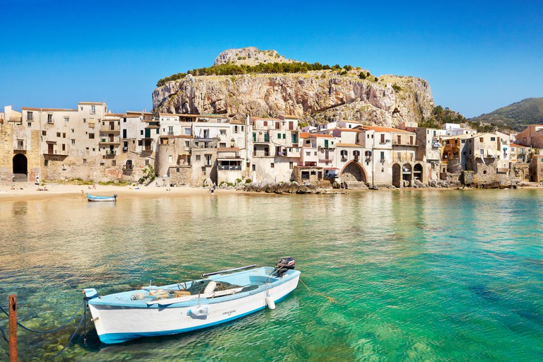 Fishing boat and medieval houses of Cefalu old town, Sicily, Italy