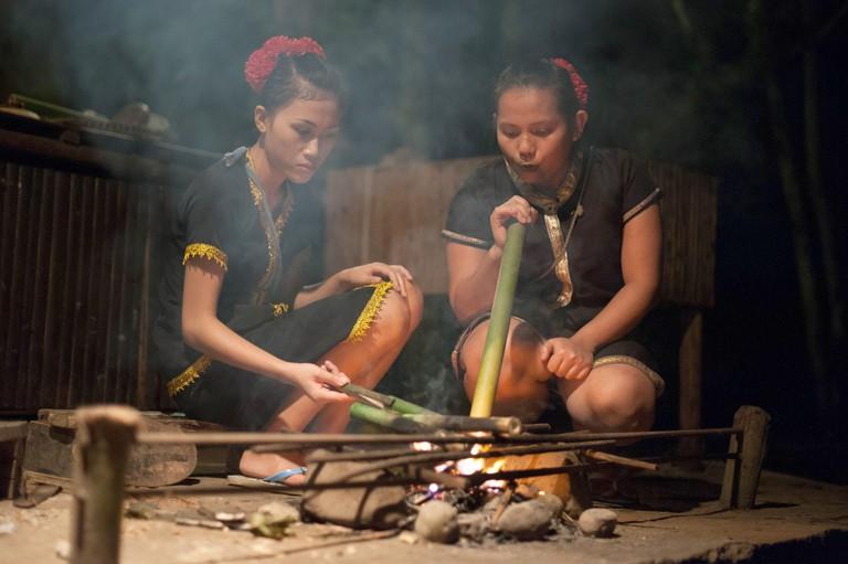 Two women wearing traditional costumes are sitting at a campfire at the Mari Mari Cultural Village near Kota Kinabalu, Malaysia, on 27 October 2014. Photo: Sebastian Kahnert - NO WIRE SERVICE -