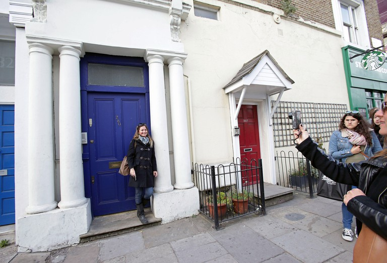 Tourists taking photographs outside the blue door of 280 Westbourne Park Road, the exterior of which featured in the 1999 film 'Notting Hill' as the place where Hugh Grant's character lived, in west London.