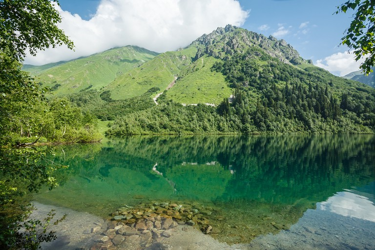 Russia. Caucasus. Mountains are reflected in the lake Kardyvach.