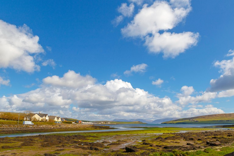 White clouds in a blue sky over Irish hills and estuary at Dingle Bay, County Kerry, Munster Province, Republic of Ireland. GFF1YF