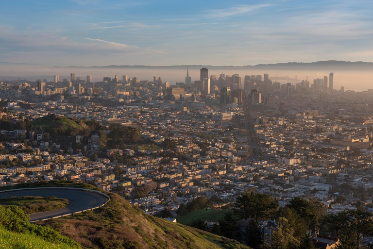 Skyline of San Francisco showing early morning fog over the bay, from the popular viewing point Twin Peaks, California, USA.