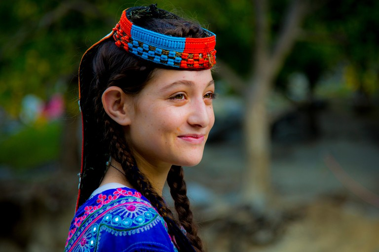 A beautiful Kalasha girl smiles as she passes a forest in Kalash Valley, Chitral, Pakistan.. Image shot 2016. Exact date unknown.