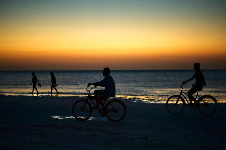 Riding bike on Holbox island beach in sunset Mexico. People cycling on the Caribbean beach at sunset.
