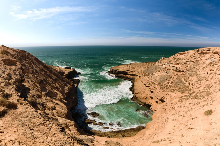 Colorful coastline with a view over a small bay with a few fishing lodges in the Souss-Massa National Park at the Atlantic Ocean in Morooco, Africa.