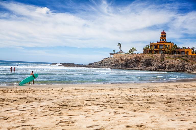 Tourists And Locals Swim And Surf In The Pacific Ocean At Los Cerritos, Todos Santos, Baja Sur, Mexico