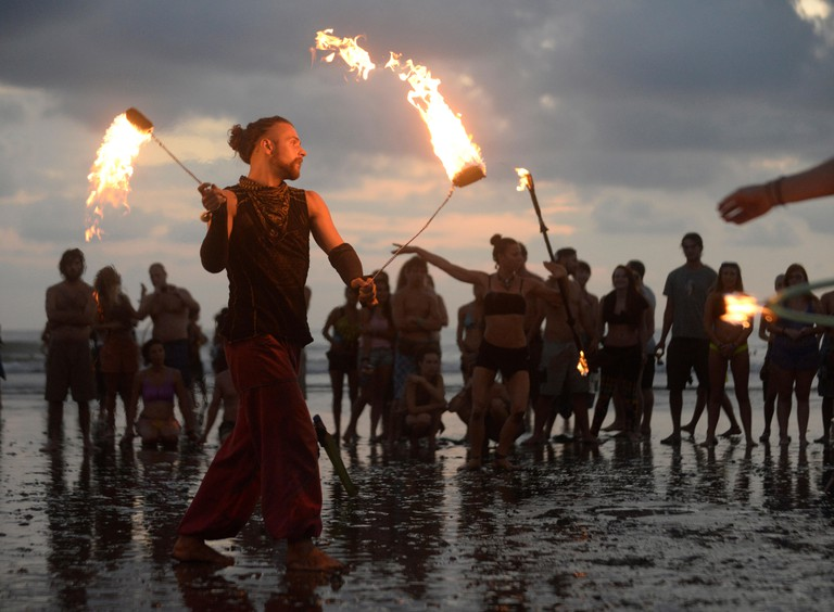 Fire dancers perform on the beach at sunset at the 2015 Envision Festival, a transformational festival on Costa Rica's Pacific Coast.