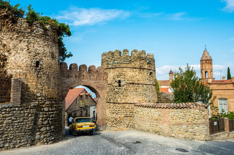 An Old Soviet Car Driving Through The Arch In The Remnants Of 18th Century Fortifications And Watchtowers; Sighnaghi, Kakheti Region, Georgia