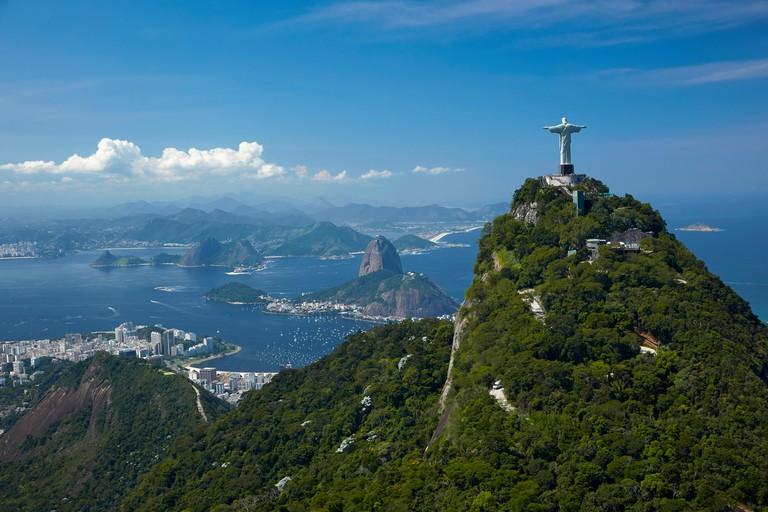Christ the Redeemer statue atop Corcovado, and Sugarloaf Mountain, Rio de Janeiro, Brazil, South America - aerial