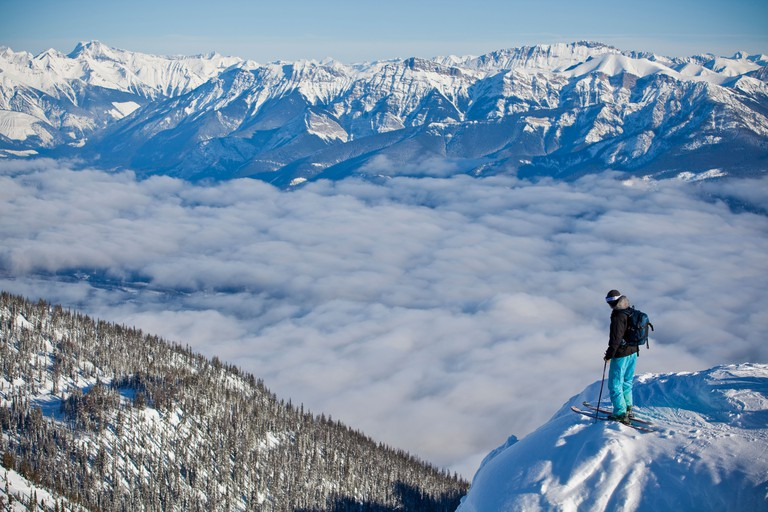 A young man enjoys the views at Kicking Horse Resort before dropping into a steep couloir. Golden, British Columbia, Canada
