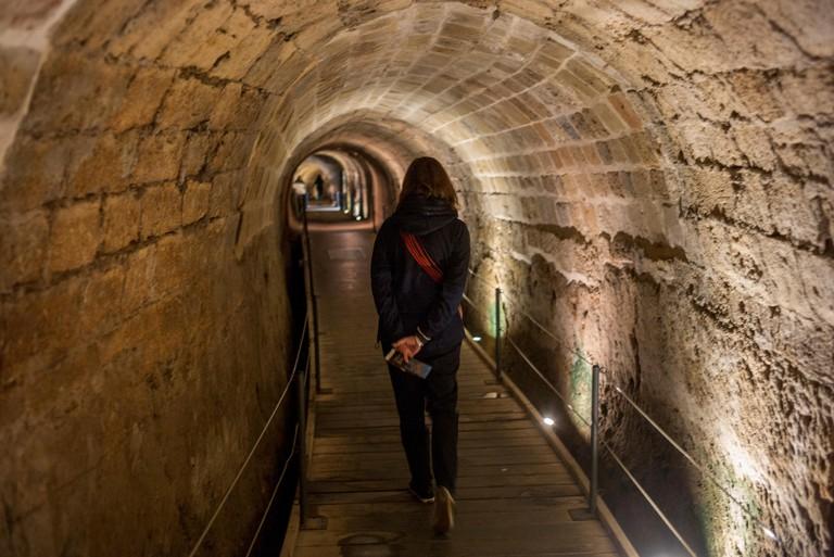 Rear view of woman walking in tunnel, Templars Tunnel, Acre, Israel