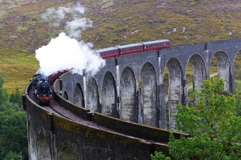 The Hogwarts Express steam train passing on Glenfinnan viaduct, Lochaber, Highland of Scotland, UK