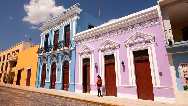 Woman walking in front of the colorful colonial buildings in the city center, Merida, Yucatan Province, Mexico, Central America.