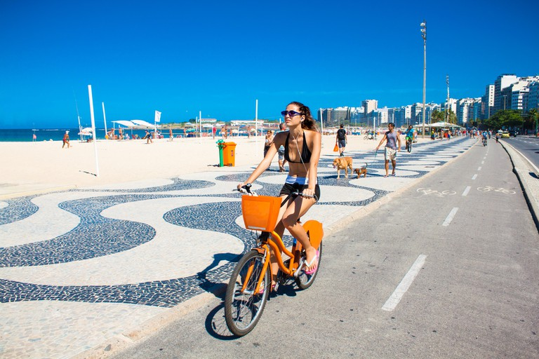RIO DE JANEIRO, BRAZIL - APRIL 24, 2015: Young Brazilian woman rides her bicycle along the boardwalk at Copacabana Beach. Rio de Janeiro , Brazia.