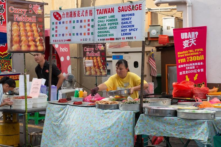 Local people preparing street food for the weekend night-market in Malacca, Malaysia